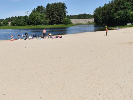 A group of visitors enjoying the Elm Brook Park beach on a clear summer day.Elm Brook Park Beach