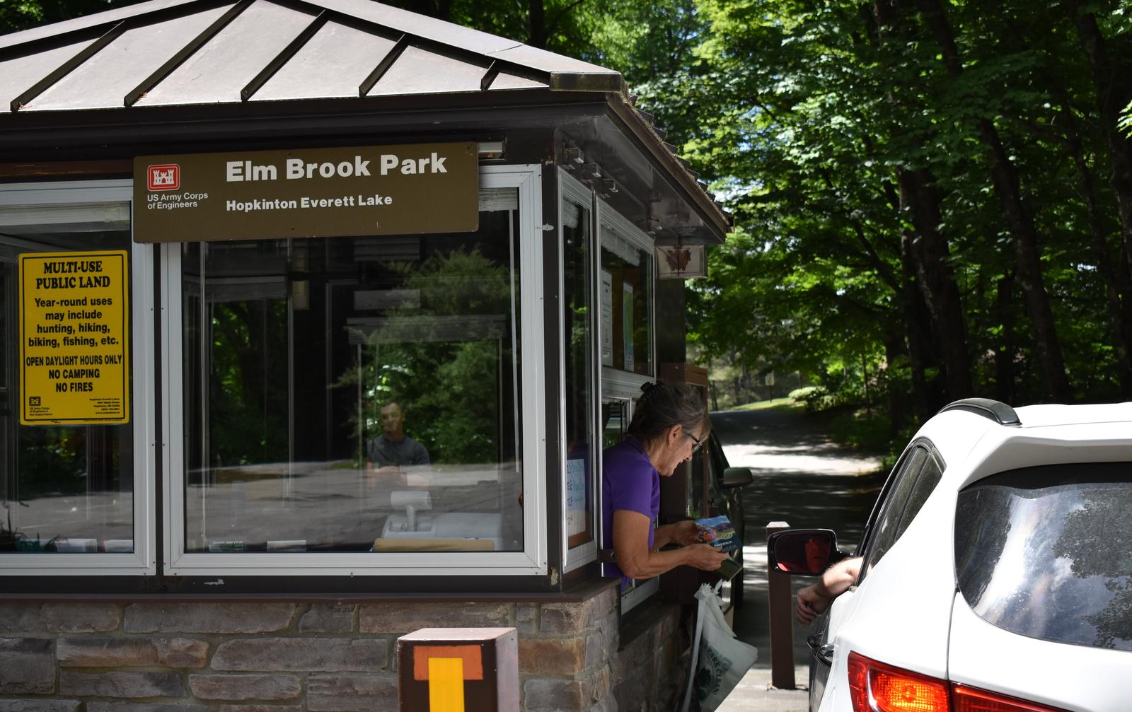 A Park Host greeting a visitor in their vehicle at the Elm Brook Park Entrance Booth.Entrance Booth