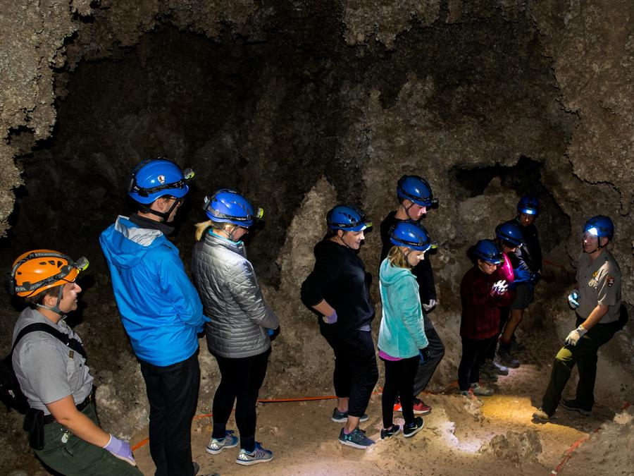 Photo of rangers and visitors in Lower Cave wearing caving helmets.Rangers and visitors in Lower Cave.