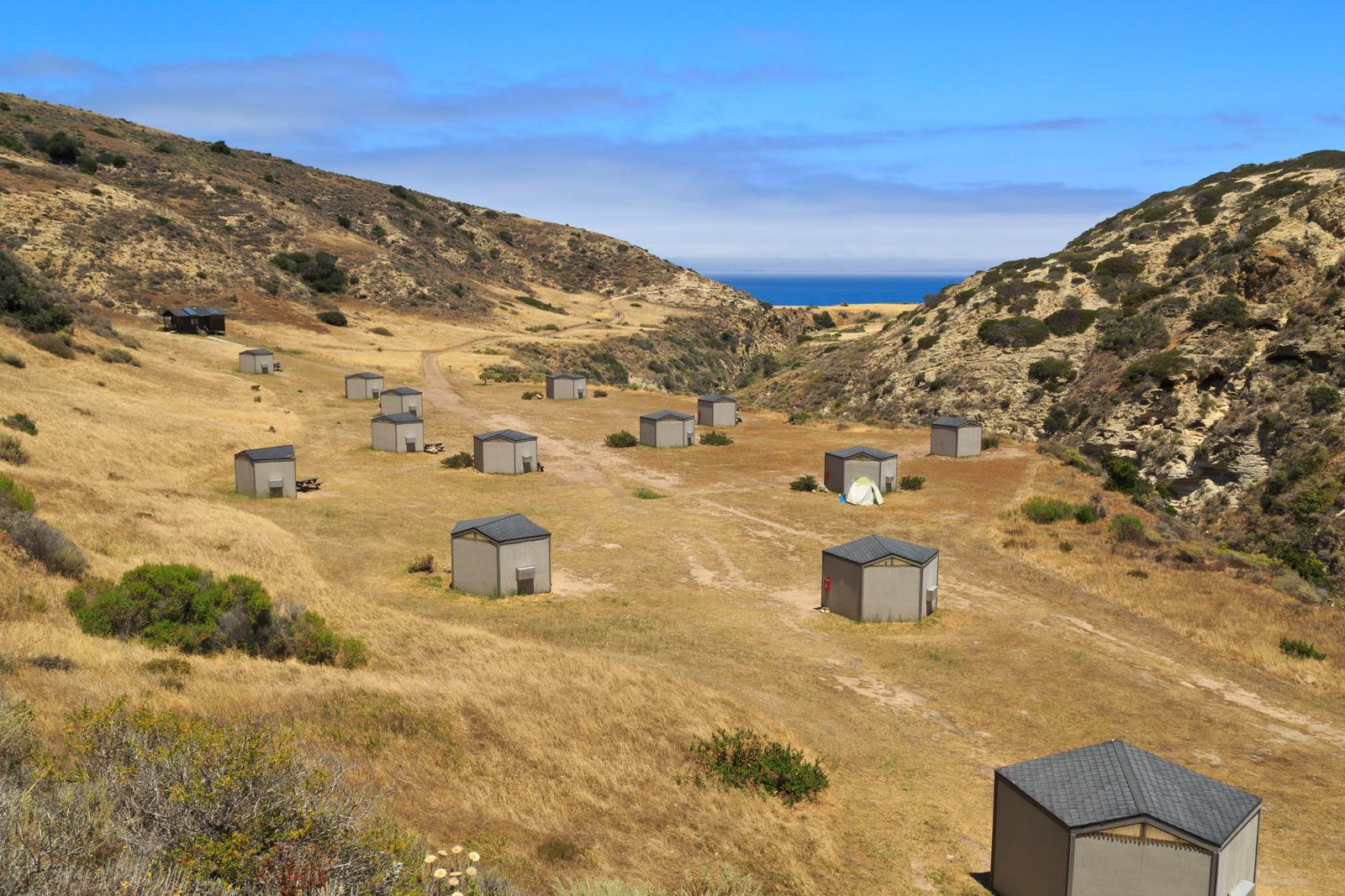 Eight foot tall wind shelters on a dry, grassy terrace overlooking the ocean. Campground, Santa Rosa Island