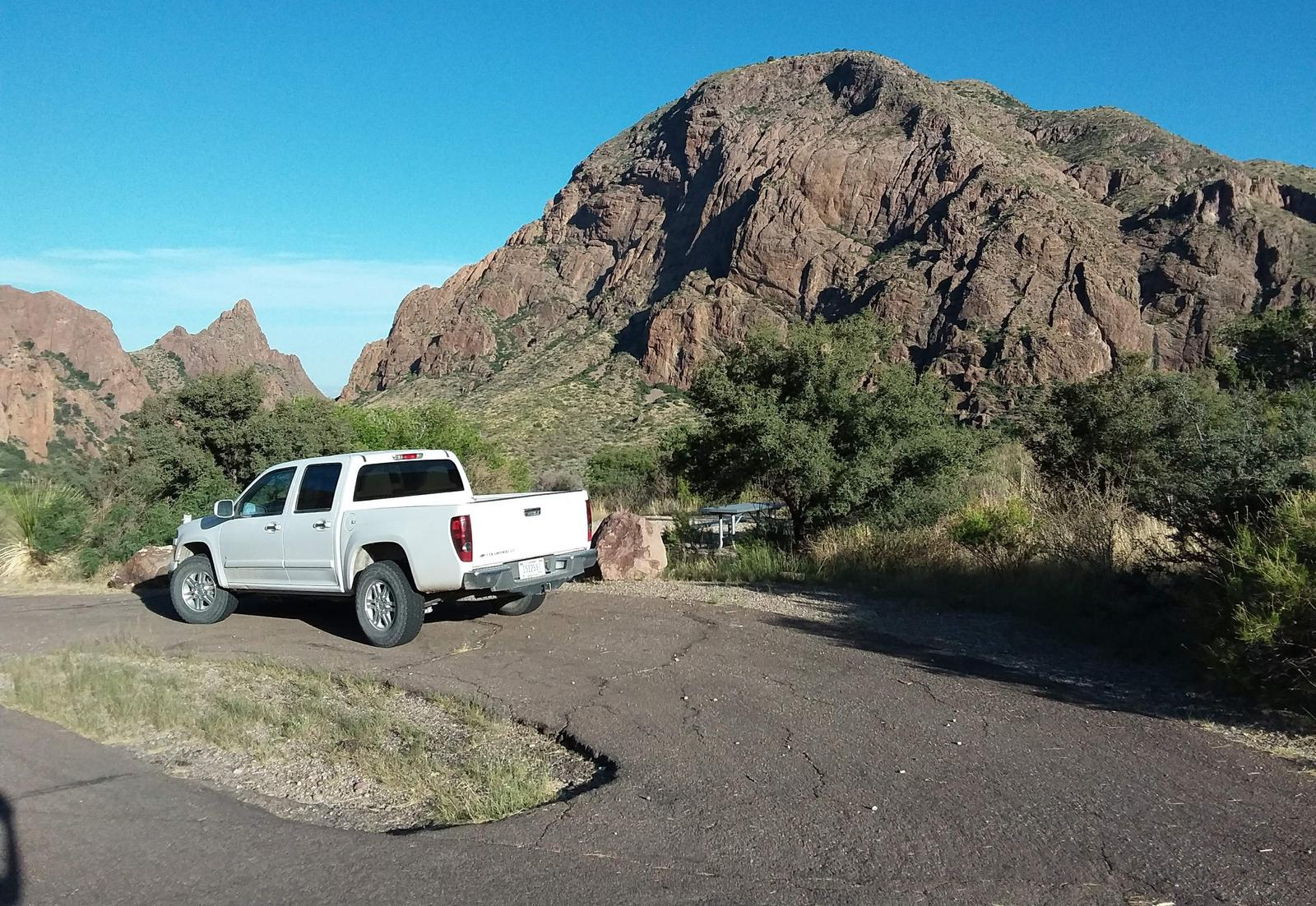 Parking area at site with mountains in the backgroundParking area