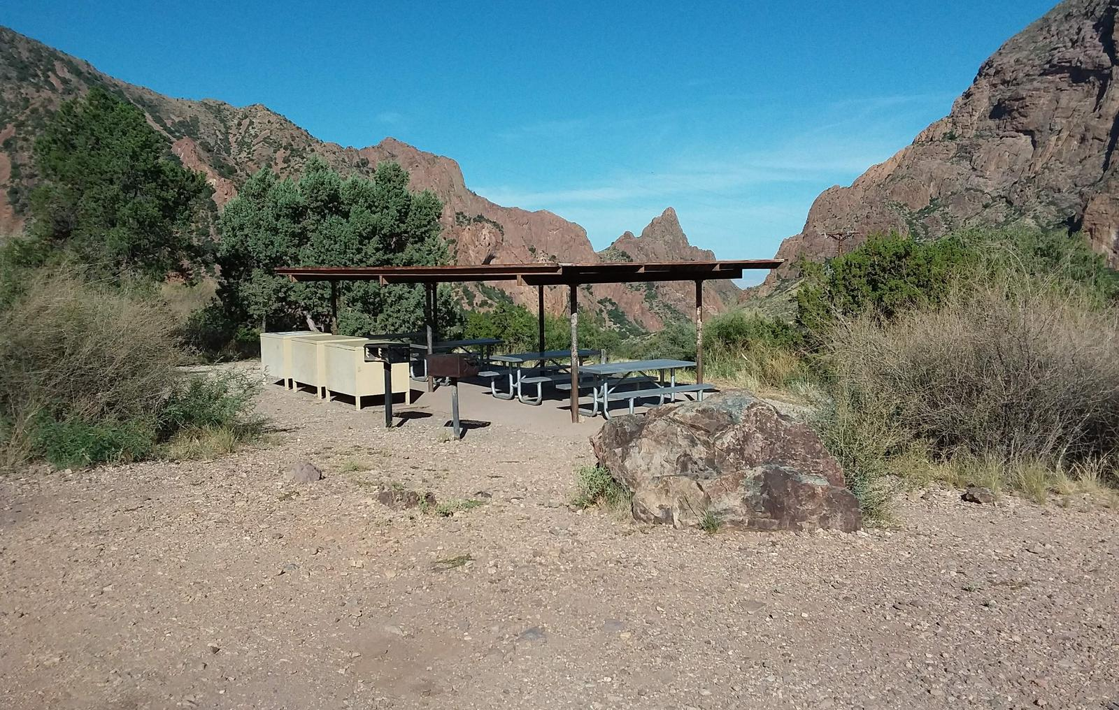 Flat area with shade structure and gathering area looking out over the mountainsShade structure and gathering area