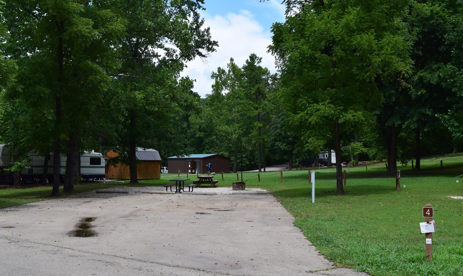 Double Campsite 4 showing double wide parking, picnic tables, lantern post, electric hookup and fire ringDouble Campsite 4