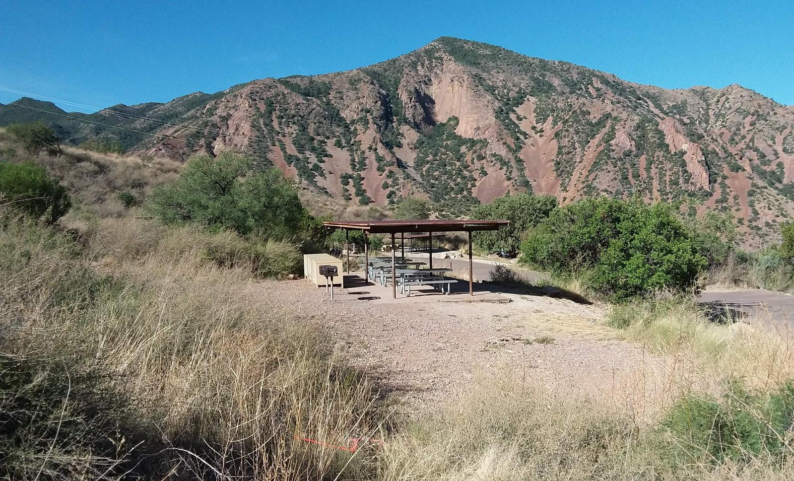 Shade structure and gathering area amidst the green and brown mountainsShade structure and gathering area