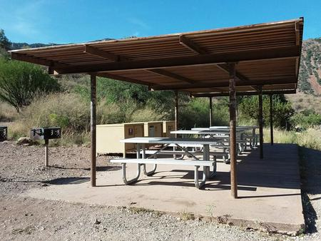 Close-up photo of the shade structure with picnic tables and bear boxes underneathShade structure with picnic tables and bear boxes