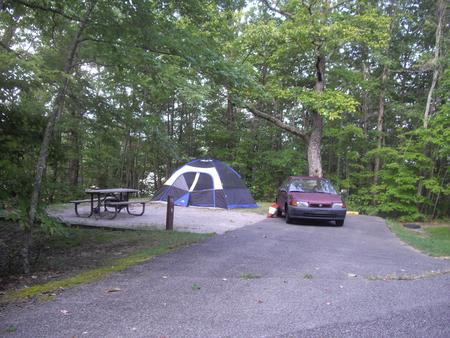 Little car parked on next to family size tent on tent pad on a gravel pad.Site number 13 in Loop A at Bandy Creek Campground.
