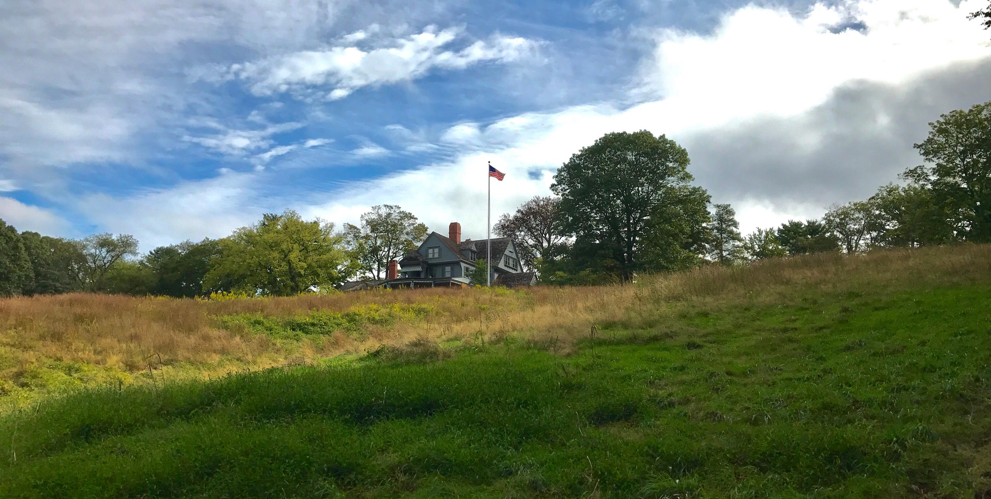 A gray house a top a grassy hill with blue sky and clouds in the background.Theodore Roosevelt's home atop Sagamore Hill.