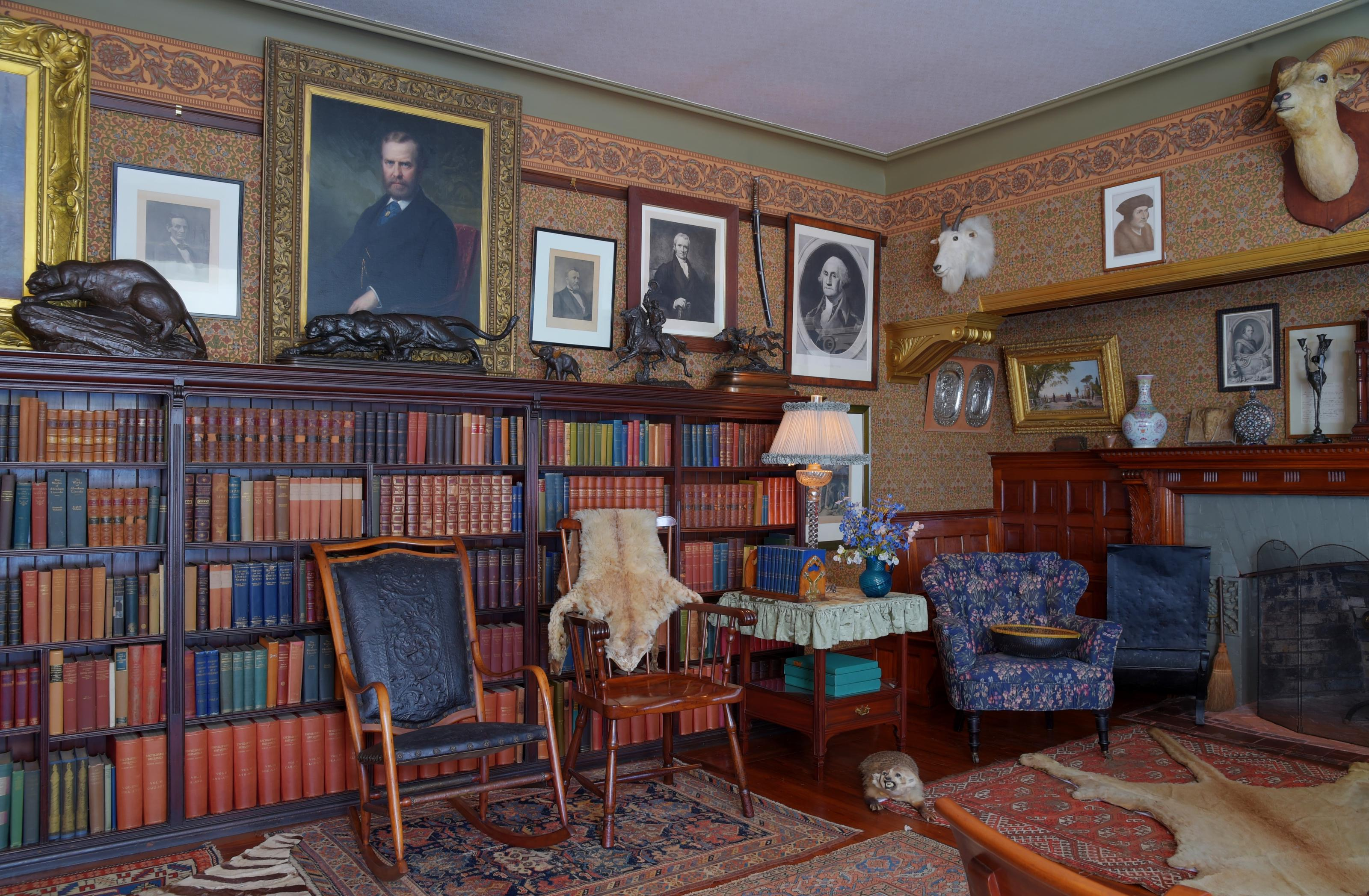A room with books, paintings, hunting trophies, chairs, and a fireplace.The library.