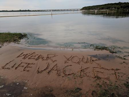 Wear your lifejacket written in sand at the lakeWear your lifejacket written in the sand at the lake