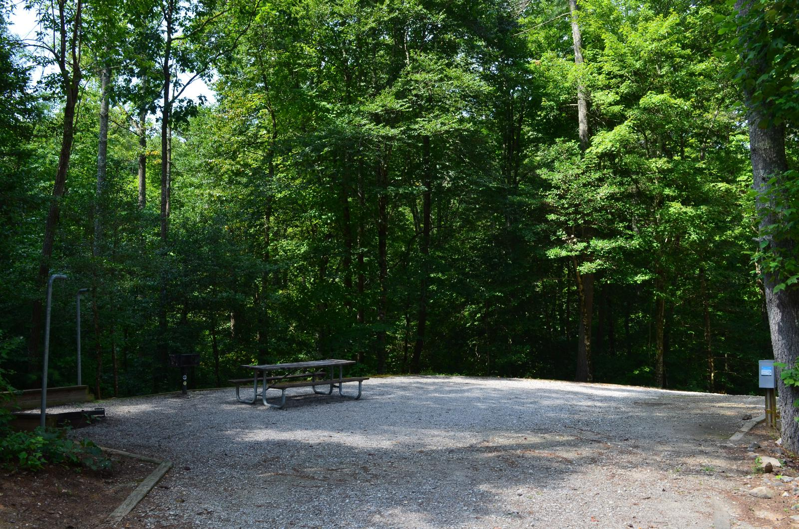 Gravel site with fire pit, grill, table
