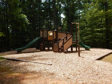 Children's playground surrounded with wood chips and nestled in the forest.Children's playground.