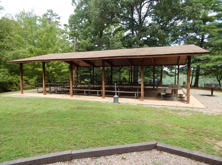 Covered shelter with tables and barbeque.A shelter with picnic tables and barbeque.