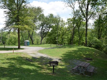 Single campsite with grill, picnic table and fire ring.