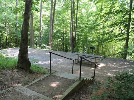 Gravel site with table, grill, fire pit with steps leading down from parking Gravel site with table, grill, fire pit and with steps leading down from parking