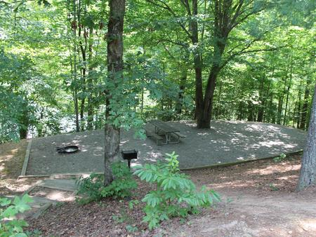 Gravel site with table, grill, fire pit with steps leading down from parking
