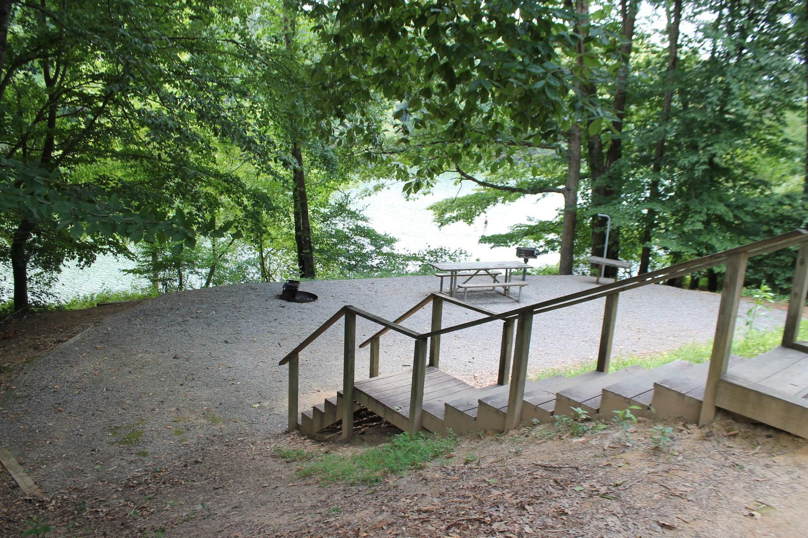 Steps leading down to gravel site with fire pit, table, grill