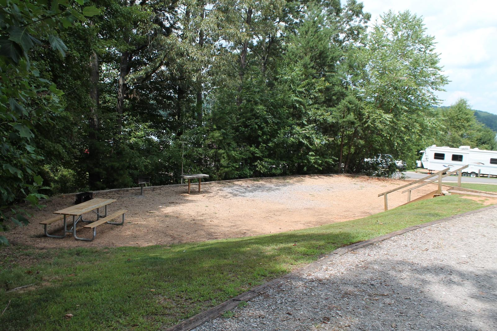 Gravel site with steps going down to table, grill, and fire pit surrounded by trees Gravel site with fire pit, table, and grill