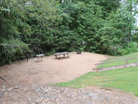 Gravel site with table, fire pit, grill surrounded by trees Gravel site with table, fire pit, grill