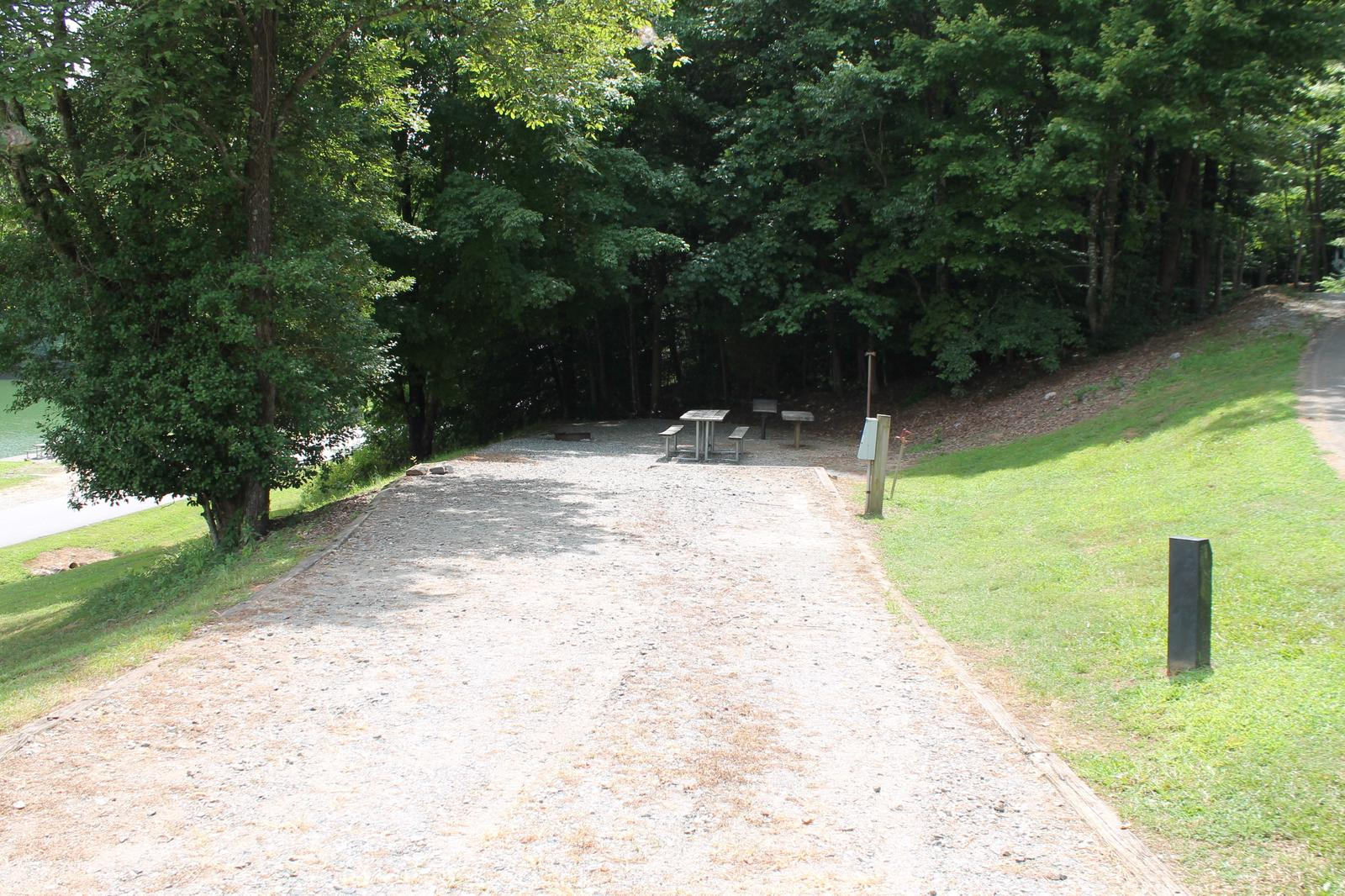 Long gravel pull in and site with table, fire pit, grill