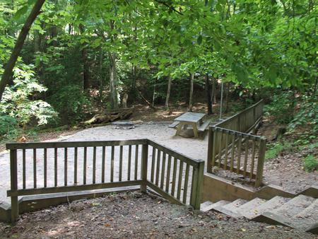 Grave site with steps leading down to table fire pit, and grill