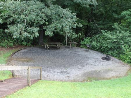 Gravel site with fire pit, table, grill and large tree coverage