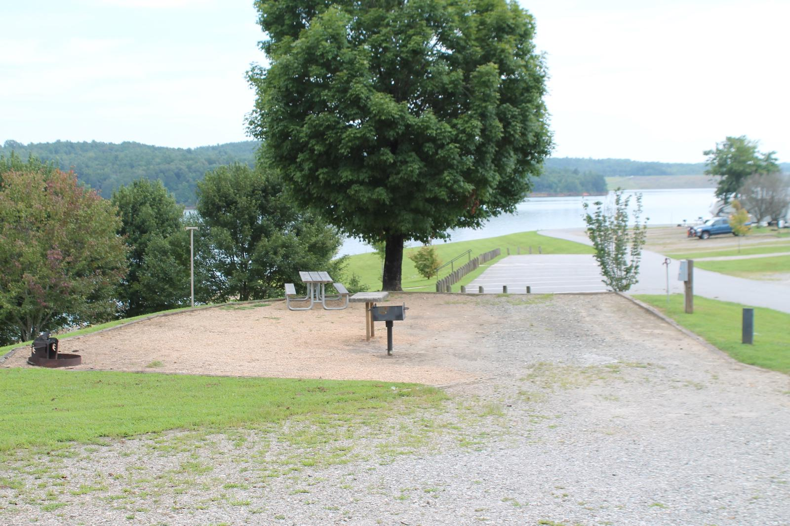 Gravel site with fire pit, table, grill, and views of the lake