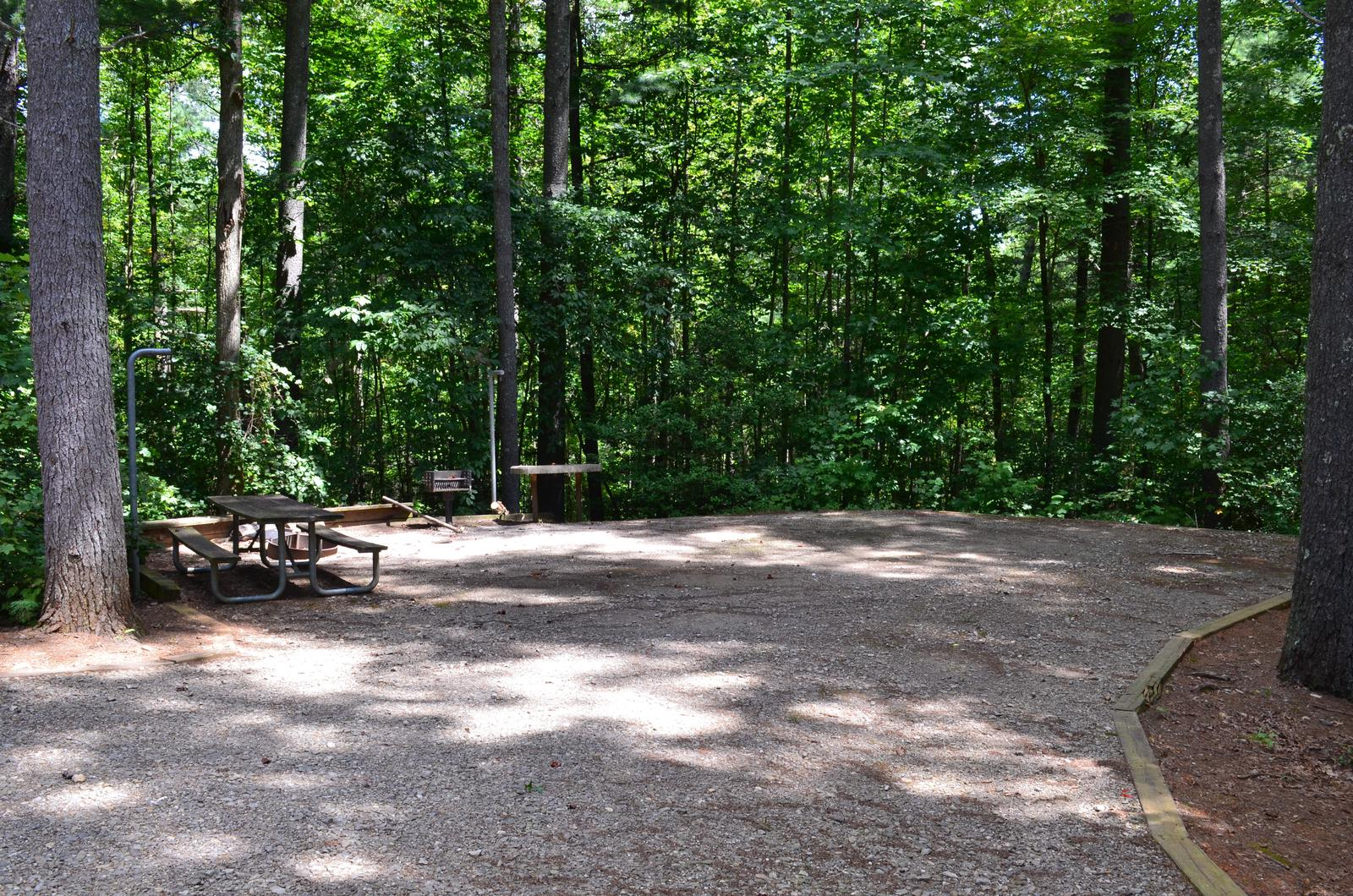 Flat gravel site with table, fire pit, grill, surrounded by trees Gravel site with table, fire pit, grill