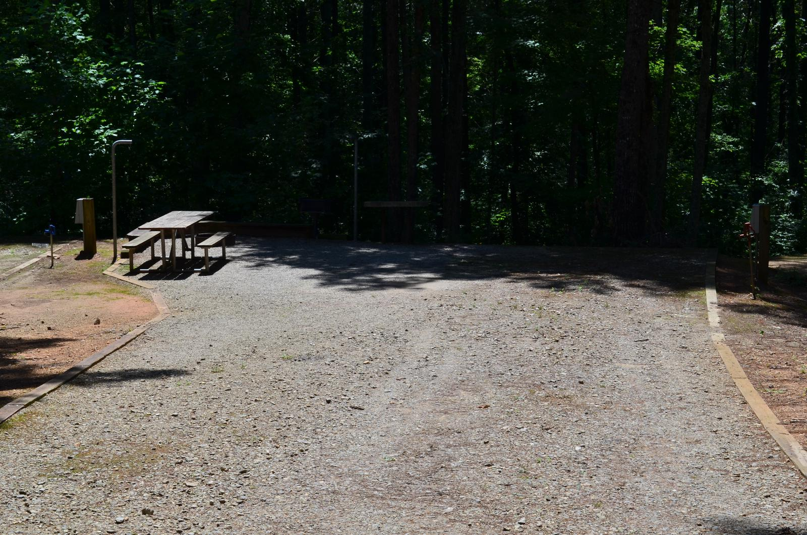Flat gravel site surrounded by trees with fire pit, grill, table
