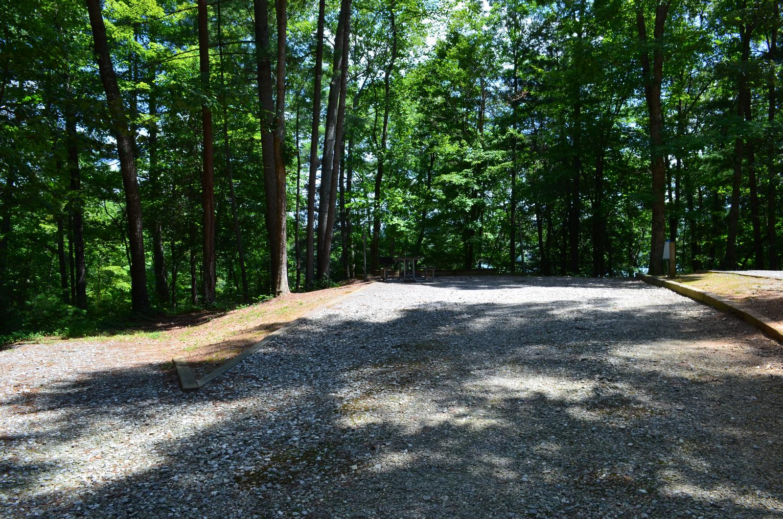 Gravel site with fire pit, grill, table, with dense tree coverage Flat gravel site with fire pit, grill, table