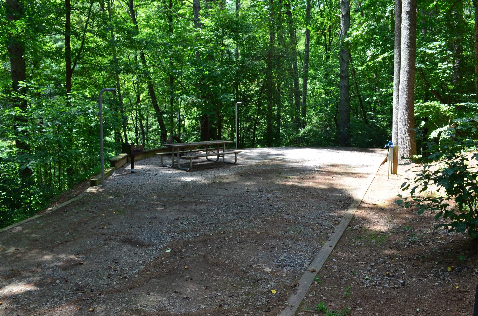 Long gravel site with table, grill, fire pit, surrounded by trees Gravel site with fire pit, table, grill
