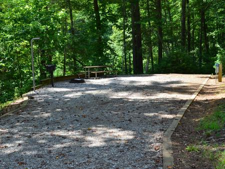 Gravel site with fire pit, table, grill and tall pines Gravel site with fire pit, table, grill
