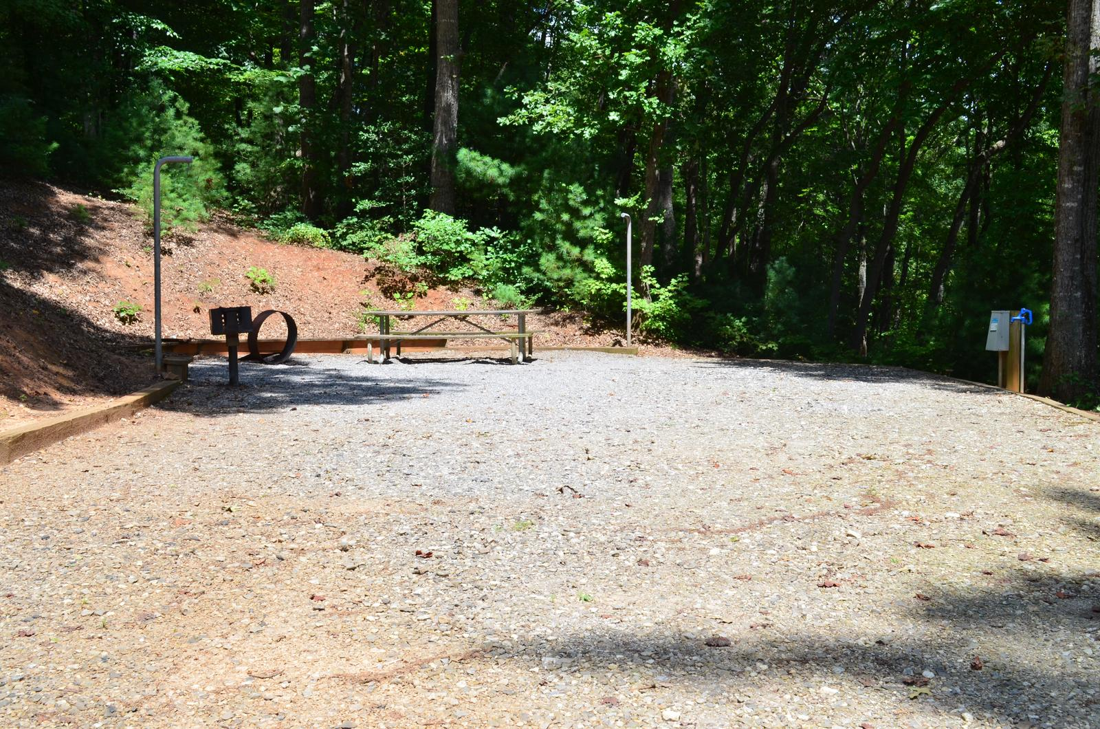 Gravel site with fire pit, table, grill, surrounded by trees Gravel site with fire pit, table, grill