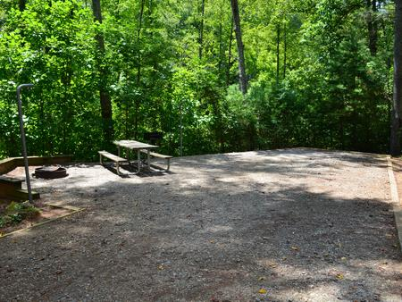 Gravel site with fire pit, table, grill