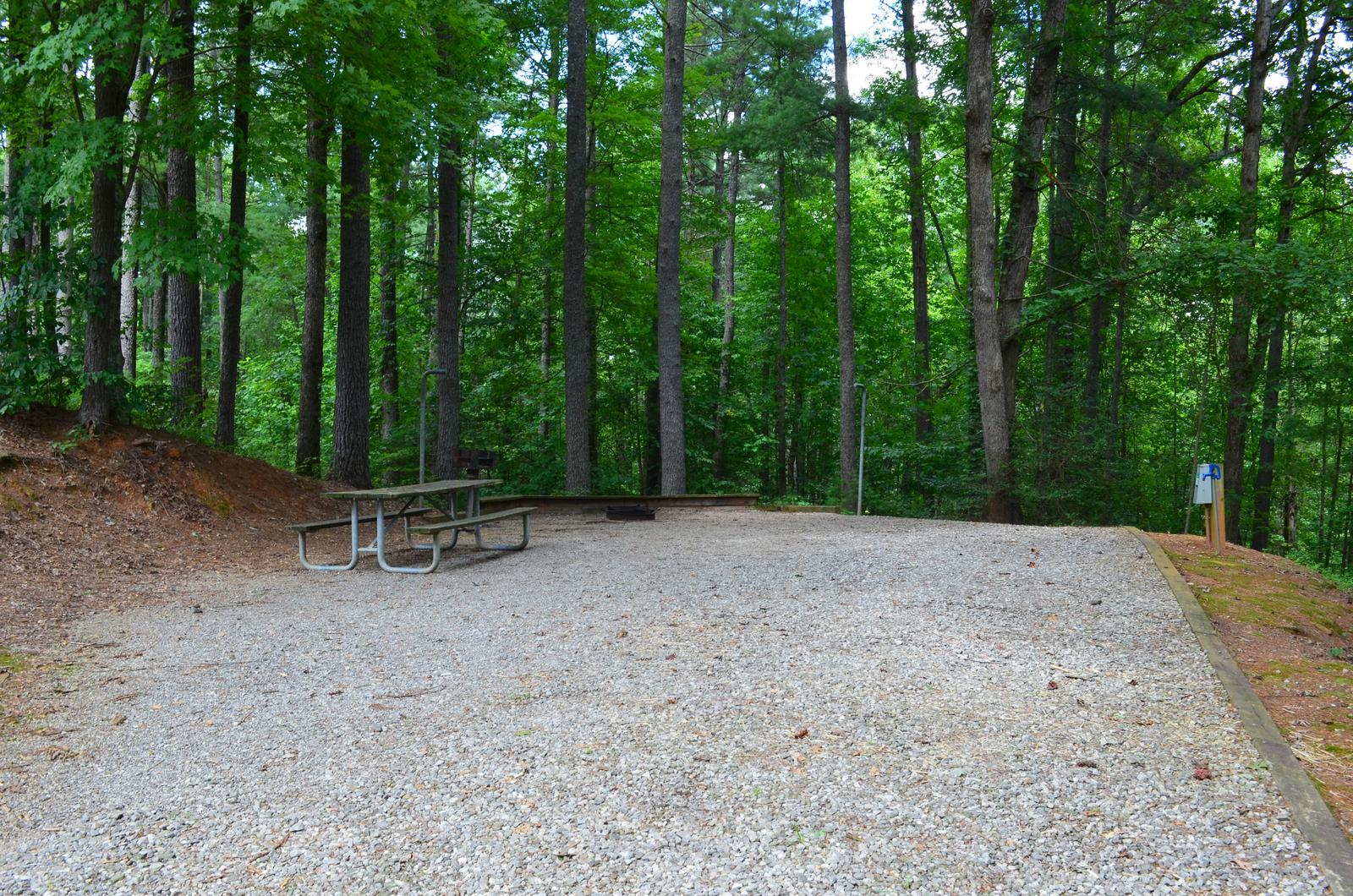 Long gravel site with fire pit, table, grill