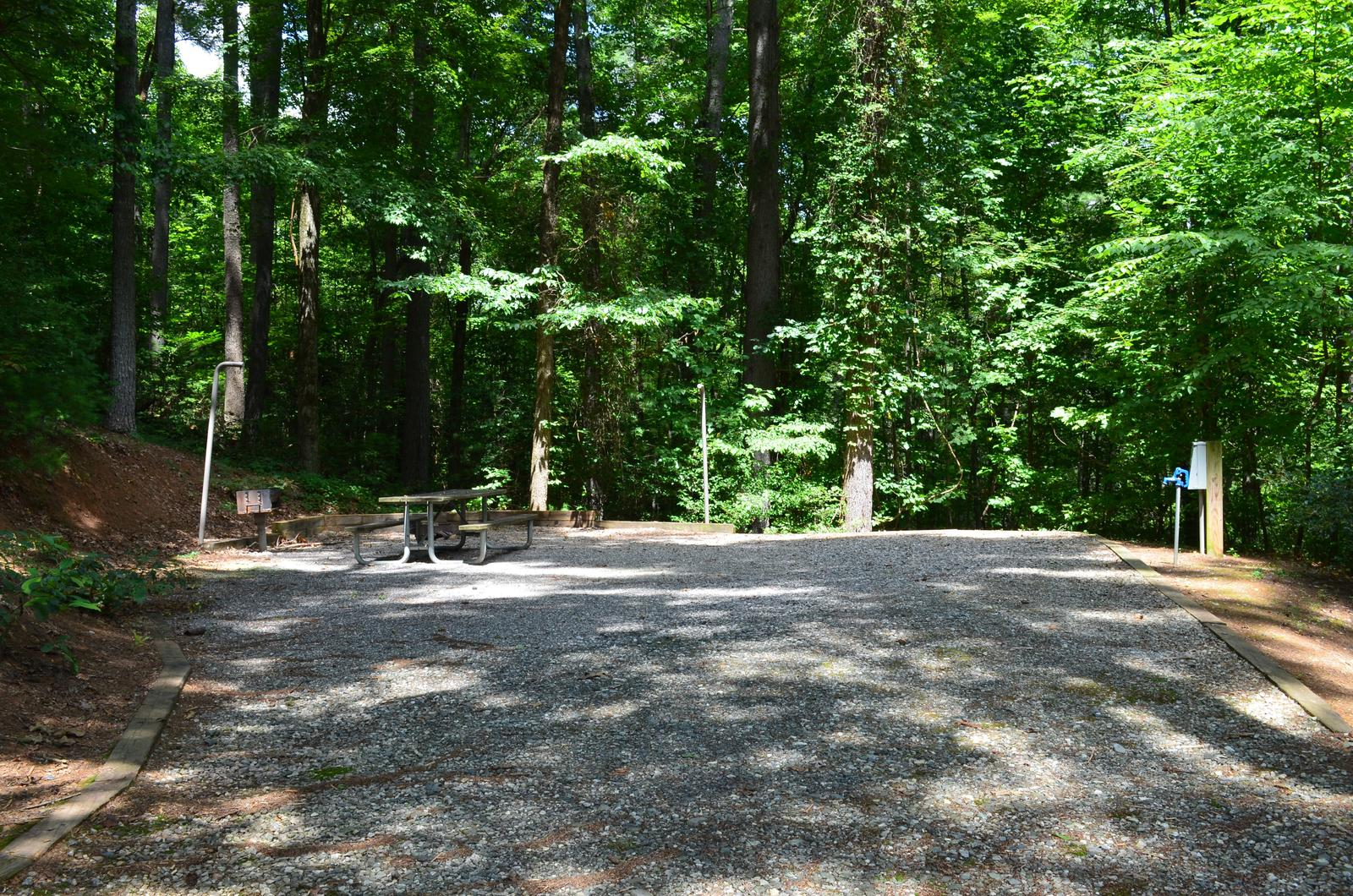 Gravel site with table, fire pit, grill, surrounded by trees Gravel site with table, fire pit, grill