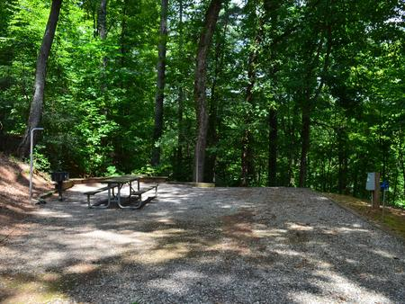 Gravel site with fire pit, table, grill with dense tree coverage Gravel site with fire pit, table, grill