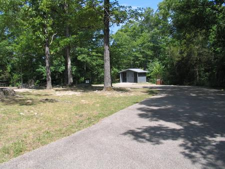 Group site showing paved parking, trash receptacles, bulletin board and vault toiletGroup site