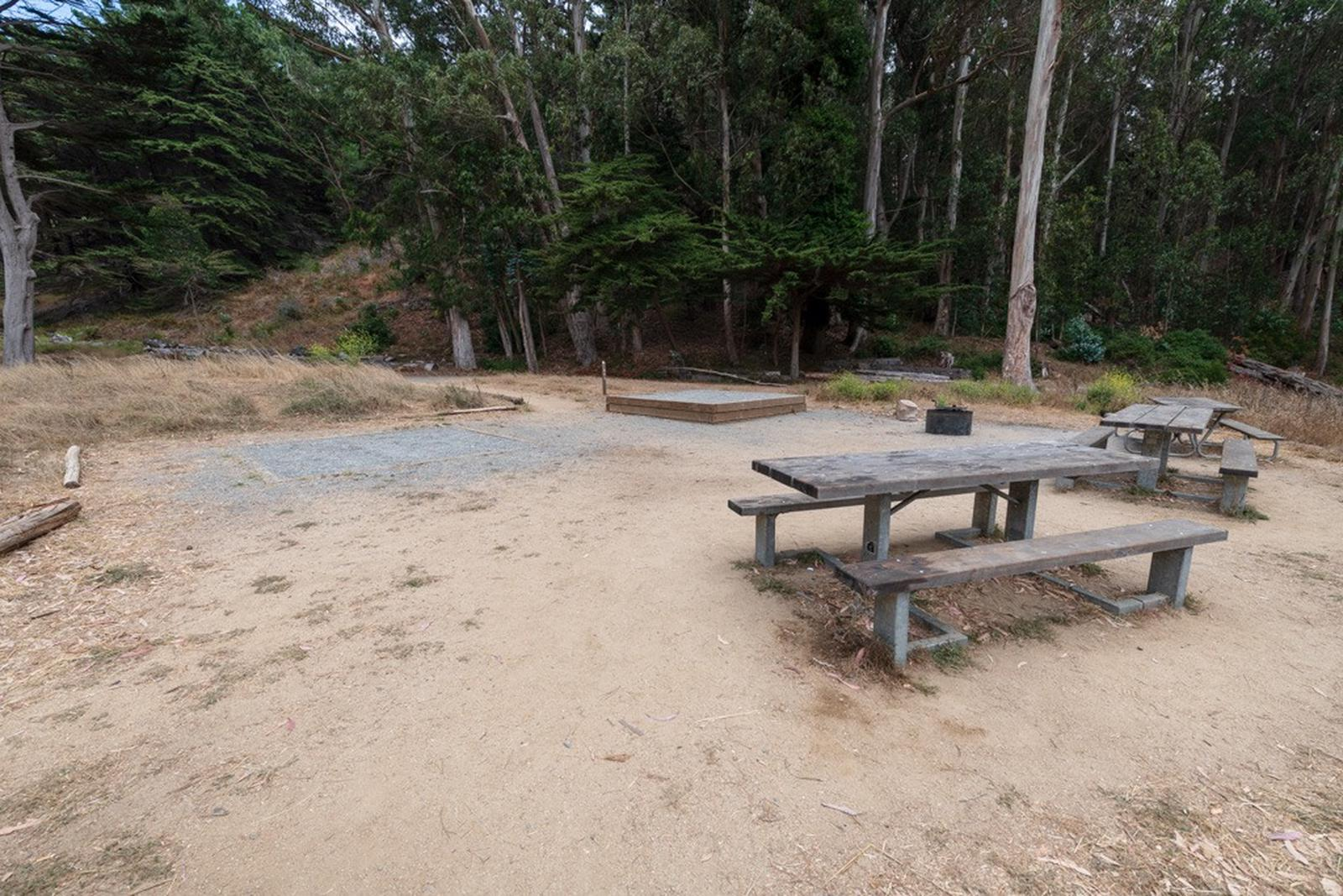Several picnic tables sit around a fire ring. A raised tent platform sits in the distance.
