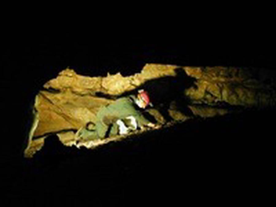 Caver crawling in a narrow passageway.