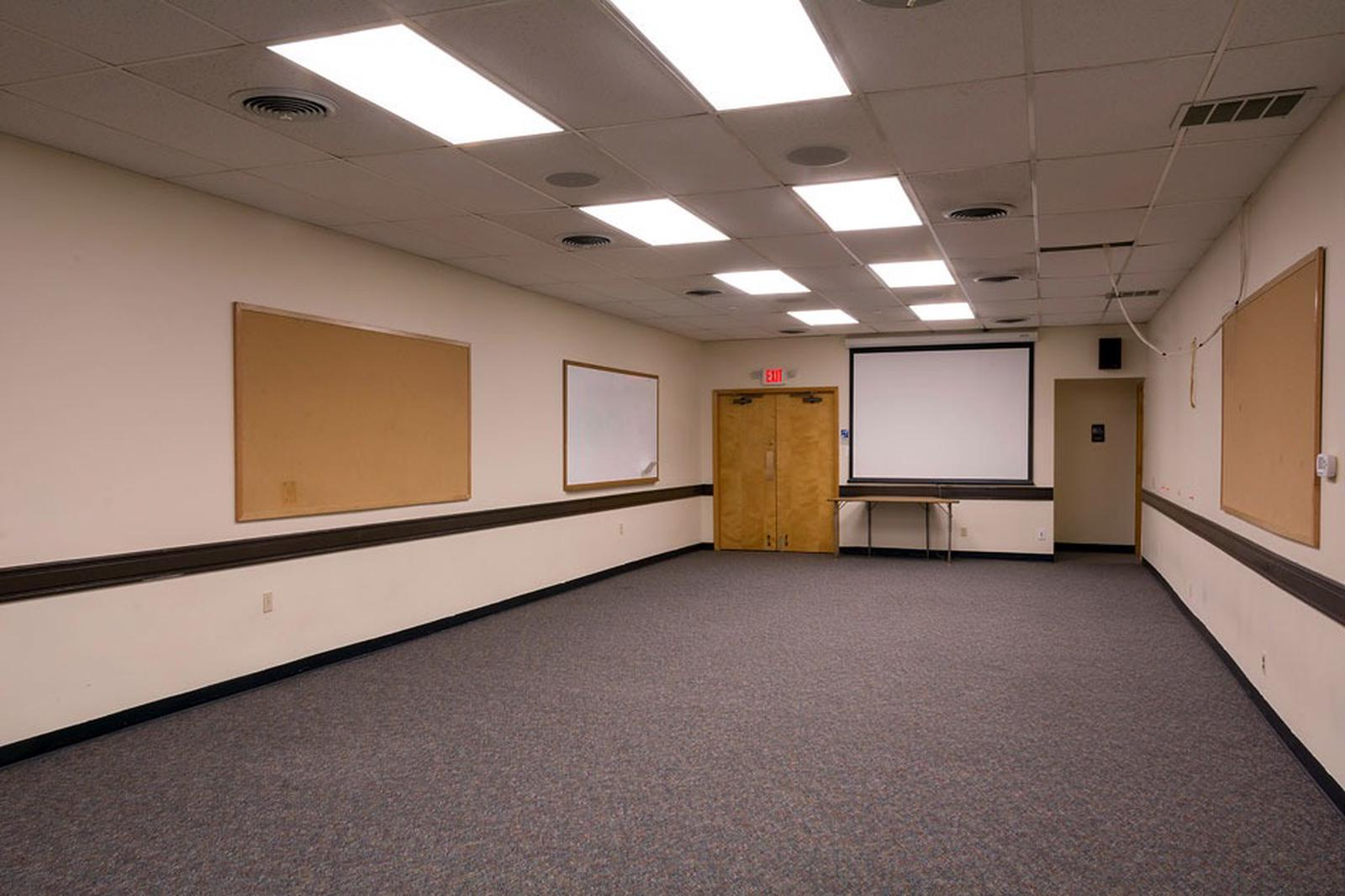 Interior view of the small conference room. Gray carpet flooring with 2 doors at the far end.  Ceiling mounted video screen on far end of room.The conference room is located inside the gym building and can accommodate 50 people. Chairs and 6 ft. tables are available in the adjacent storage room.