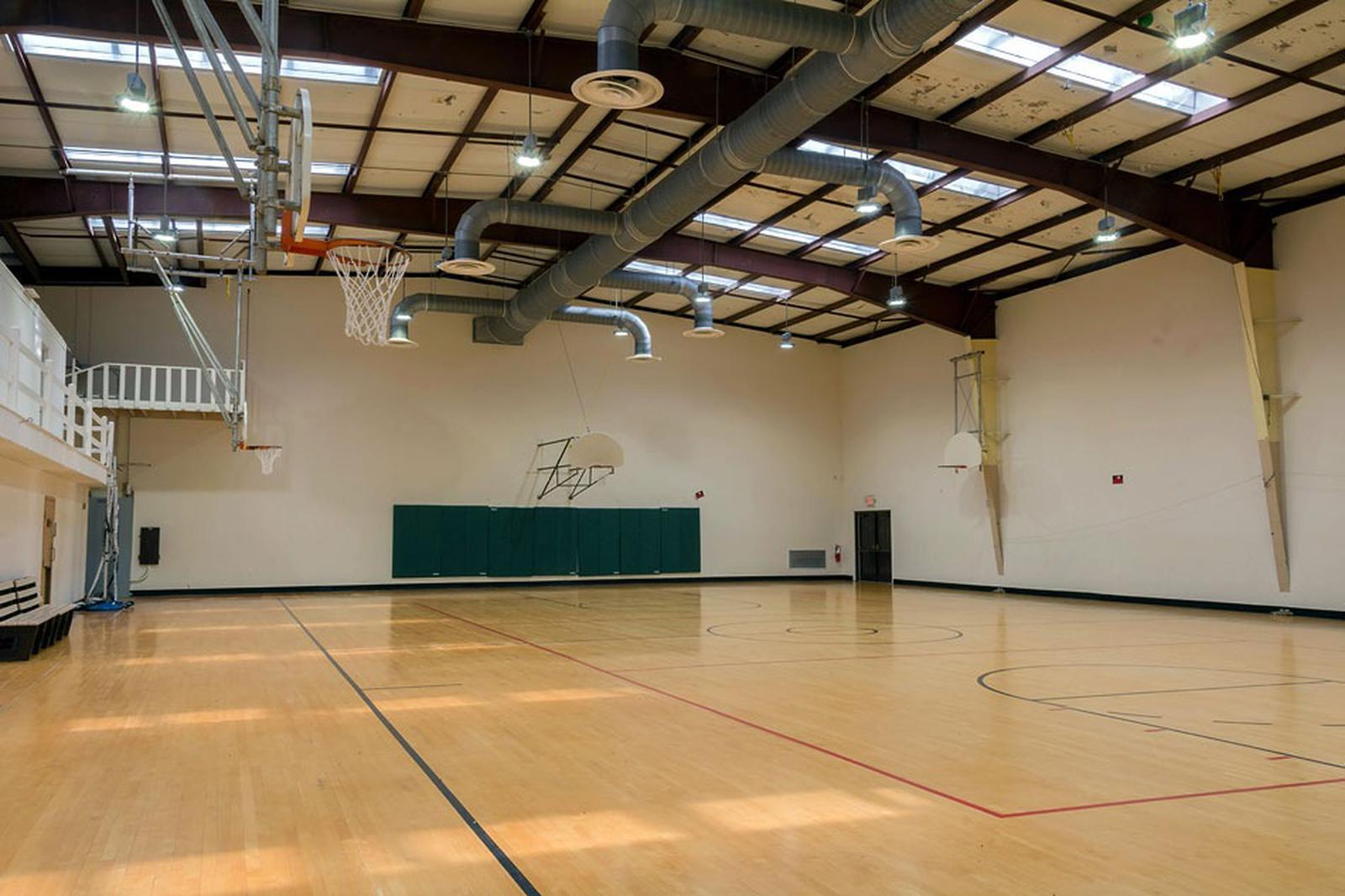 Interior view of gymnasium.  Standard size wooden marked floor with 6 basketball backboards/nets.Interior view of gymnasium.  Standard size wooden marked floor with 6 basketball backboards/nets.  The building has air conditioning and heat.  Four small classrooms are accessible from the gymnasium.
