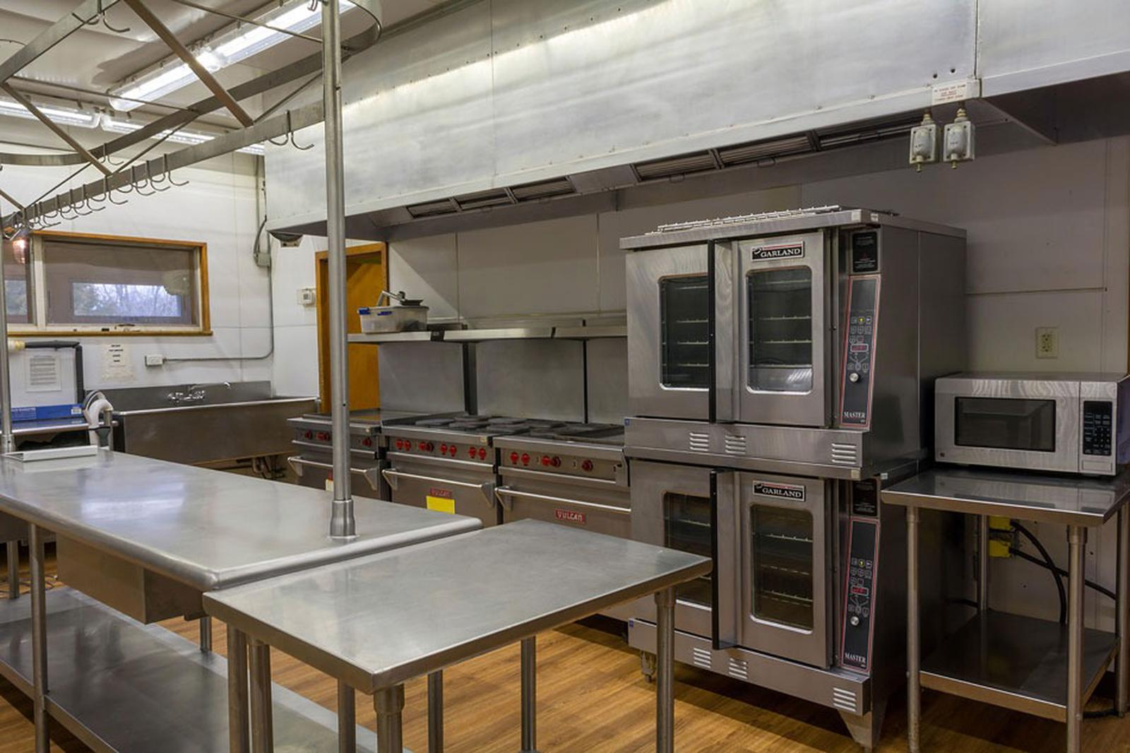 Interior view of kitchen showing stainless prep tables, microwave, convection ovens, 3 gas ranges, vent hood and double sink.                                                                                    Interior view of the kitchen which is connected to the dining hall. The area has heat and air conditioning. Visible equipment includes stainless prep tables, microwave, convection ovens, 3 gas ranges, vent hood and double sink.