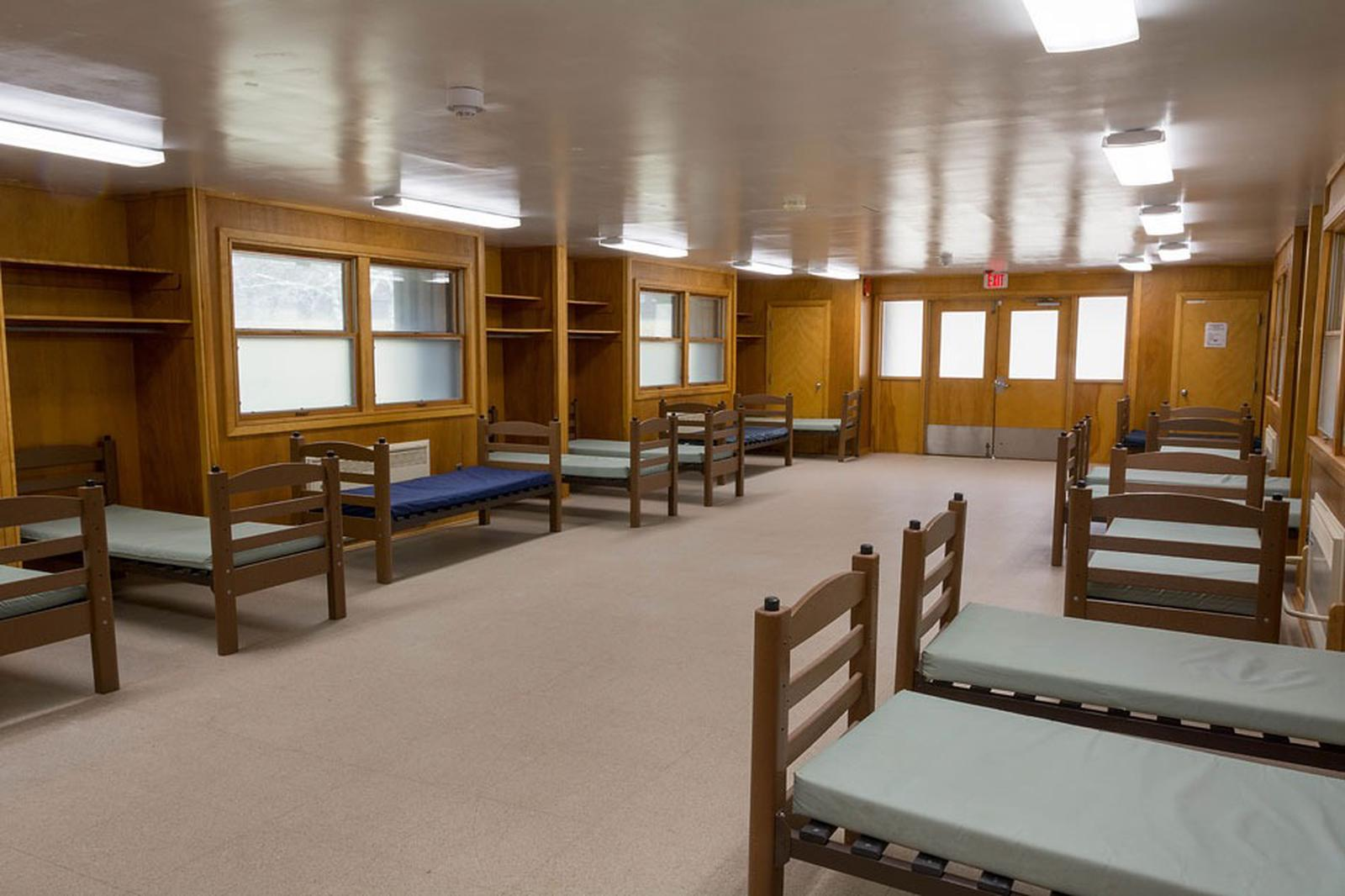 Interior view of 1 dormitory wing. Vinyl floor with wooden walls, 2 double windows, 1 double door with window panels.  10 single beds with vinyl covered mattresses.Each dormitory is heated and  accommodates 30 overnight guests.  There are 15 single beds on each of the 2 connected wings.  Each wing has a separate room with 1 single bed.  There are a set of bathrooms for each wing and a supply closet with cleaning equipment.