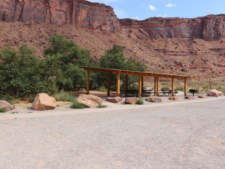 Big Bend Group Site A shade shelter with picnic tables underneath. Parking area in the foreground and red rock cliffs line the horizon.