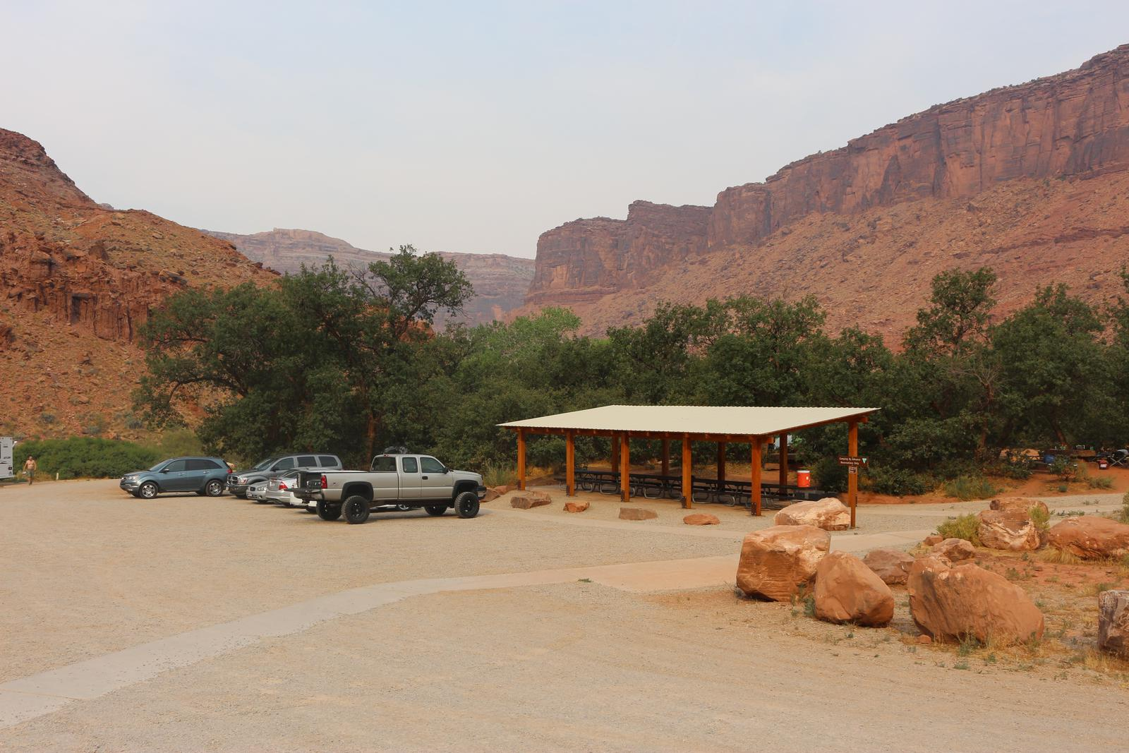 Big Bend Group Site A parking area with six cars parked next to the large shade shelter. Tall, red rock cliffs line the horizon.