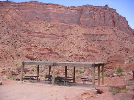 Close up of the Big Bend Group Site C shade shelter and picnic tables. Large, red rock cliff walls in the distance.