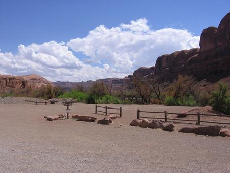 Gold Bar Group Site D parking and tent area. Site is next to the Colorado River with tall, red rock cliffs in the distance.