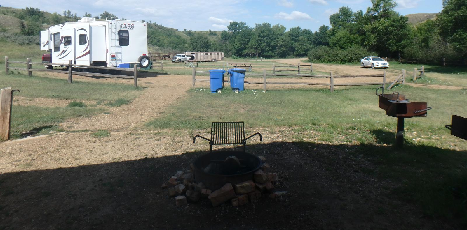 Site looking east from the picnic area with fire pit and grill int he forefront. Site from the picnic area.