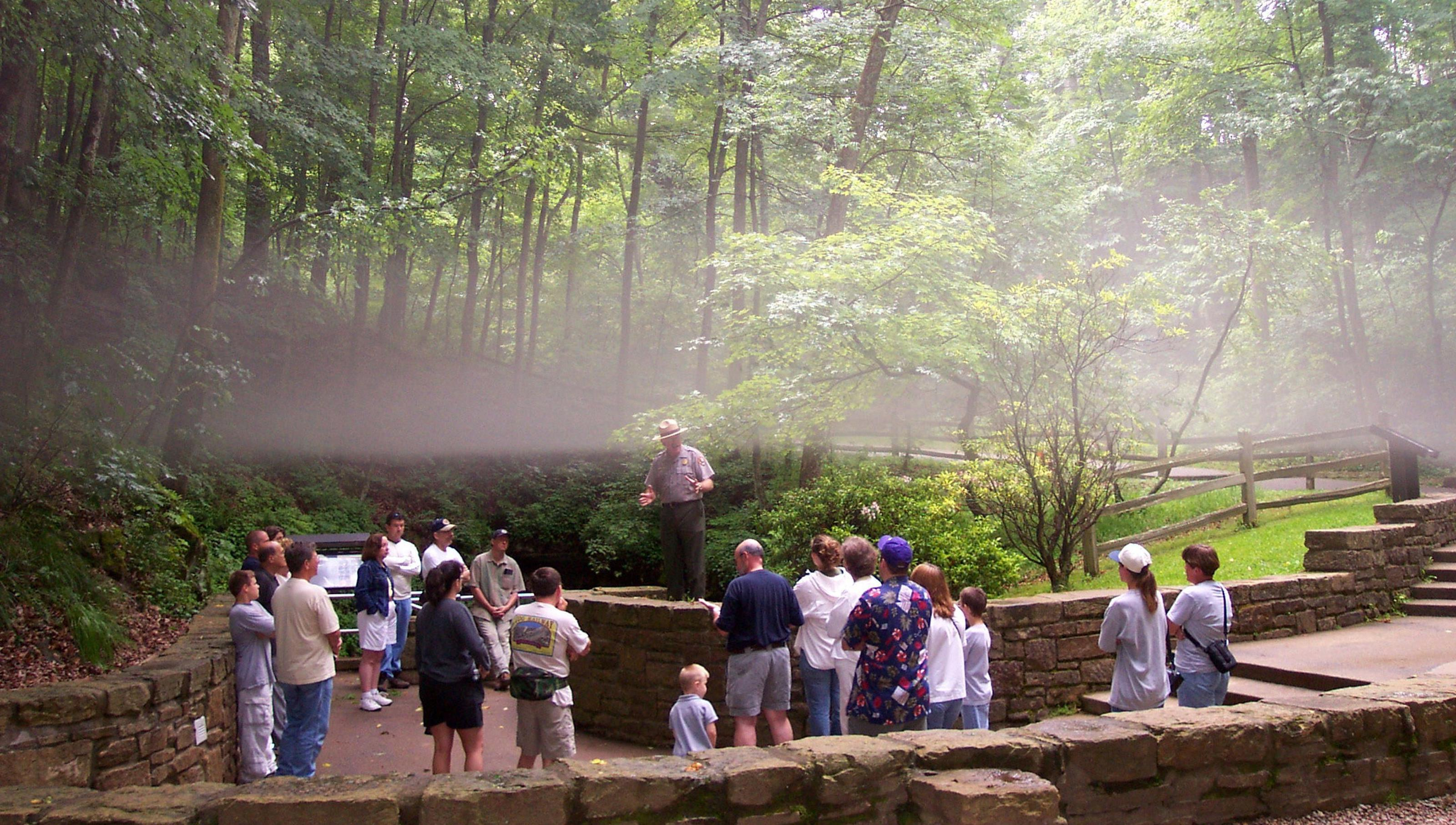 A fog layer separates over a waiting tour as cool cave air meets summer swelter at the Historic Entrance.