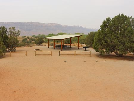 Ken's Lake Group Site B shade shelter, picnic tables, standing grill, fire pit, and parking area..